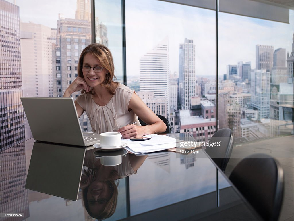 Woman working on computer with cityscape in background : Stock Photo