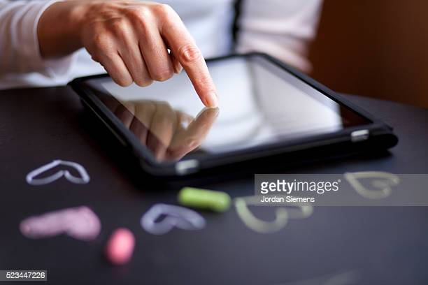 Woman working on digital tablet, close-up of hand