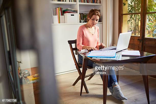 Woman working on finances and taxes at home.