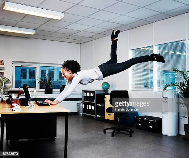Woman working on her computer floating above the f