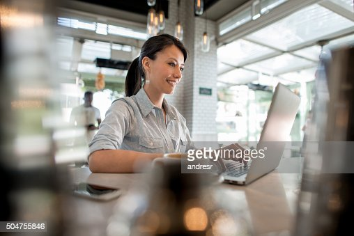 Woman working on her laptop at a cafe
