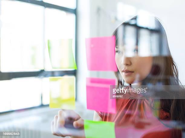 Femme travaillant sur son todos regardant au verre