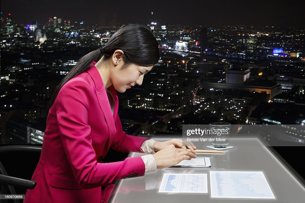 Woman working on i-pad and interactive table : Stock Photo