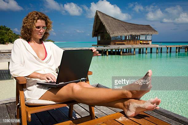 Woman working on laptop by the pool on vacation