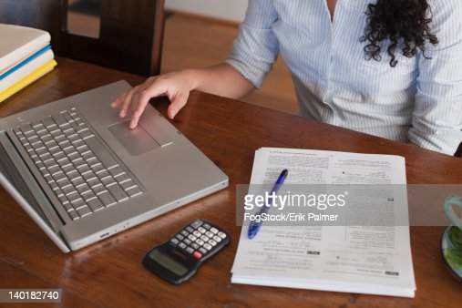 Woman Working on Laptop Computer, Calculator and Tax Documents at Dining Room Table, Detail : Stock Photo