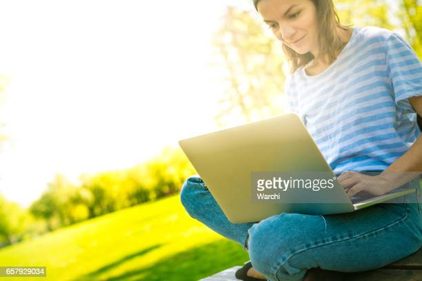 Woman working on laptop in park