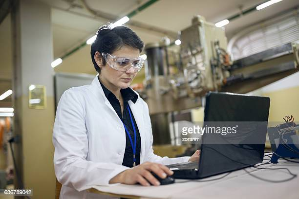 Woman working on laptop in production line