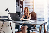 Woman working on laptop sitting at her desk in office.