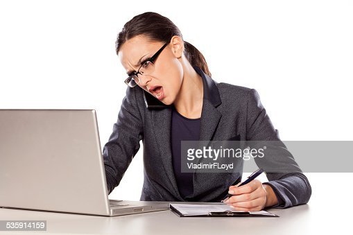 Woman working on laptop, talking on the phone and writing : Stock Photo