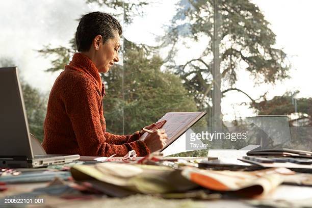 Woman working on pad at desk