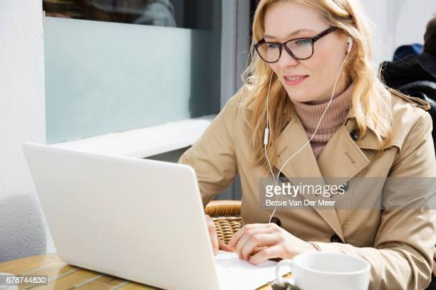 Woman working on portable information device in outdoor cafe.
