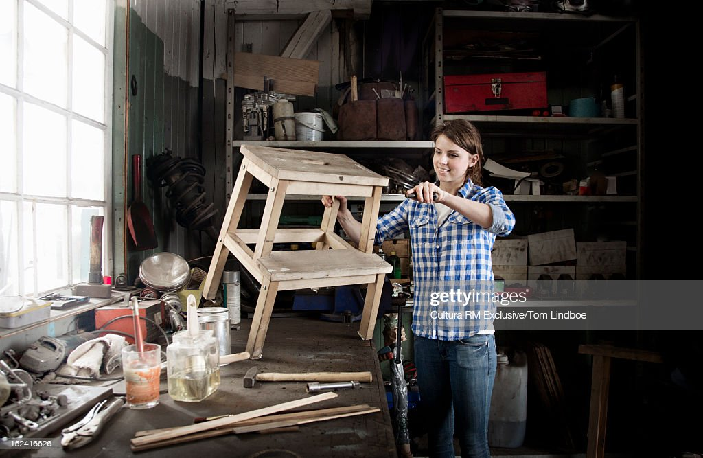 Woman working on stool in workshop : Stock Photo