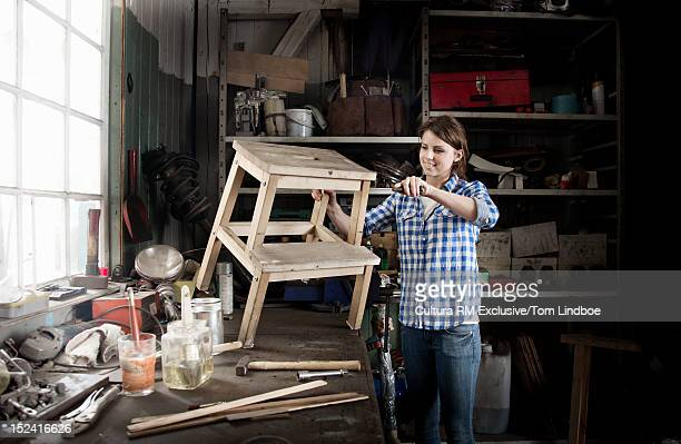 Woman working on stool in workshop