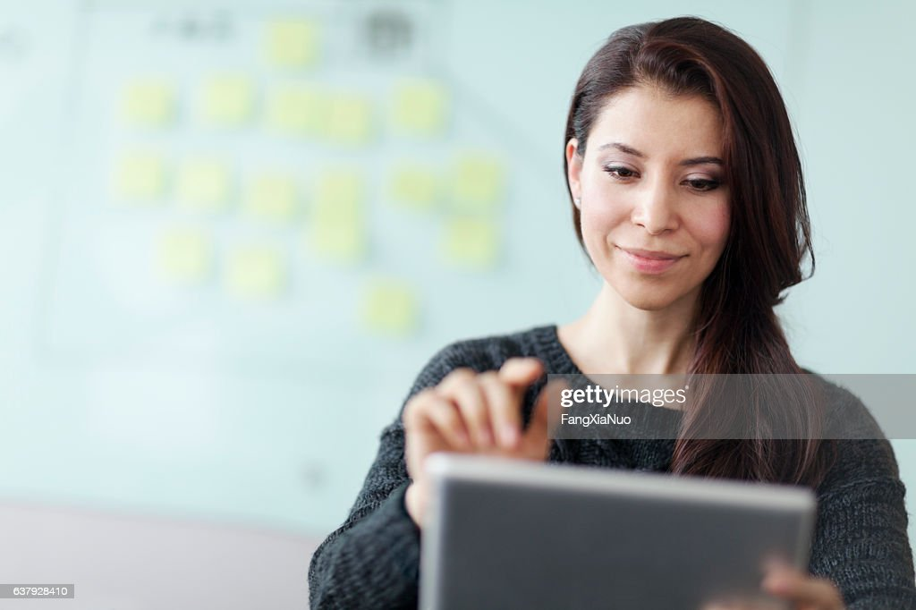 Woman working on tablet computer in studio office : Stock Photo