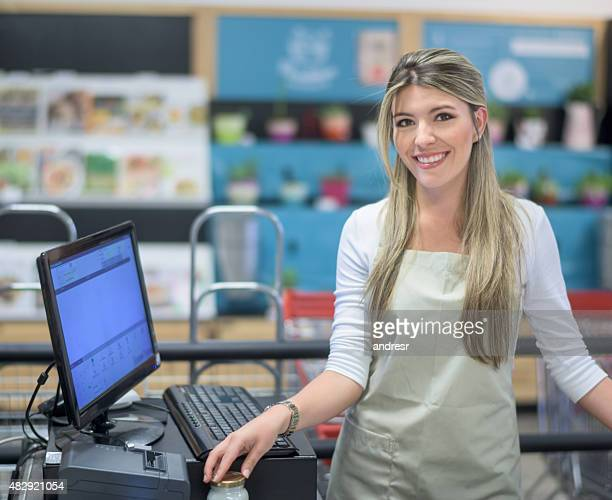 Woman working on the cashier at a food market