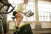 Fitness woman on bicycle doing exercising at gym. Fit young female working out on gym bike.
