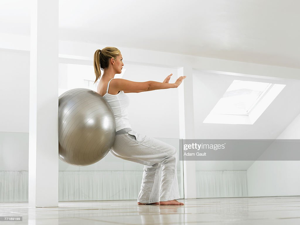 A woman working out with a pilates ball : Stock Photo