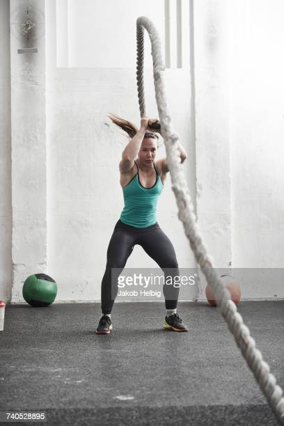 Woman working out with battle rope in cross training gym