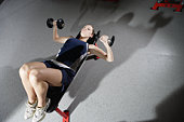 Woman working out with dumbbells in gym, elevated view
