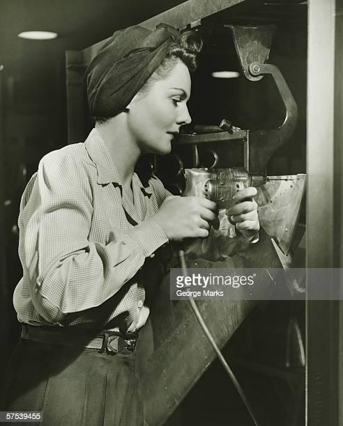 Femme travaillant avec perceuse électrique en usine (B & W