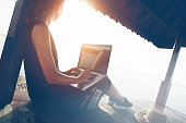 Woman working with laptop on the beach in shadow shelter. Blurry effect, lens flares effect, intentional sun glare