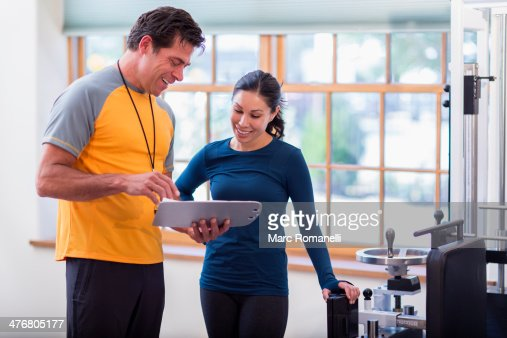 Woman working with personal trainer in gym : Stock Photo