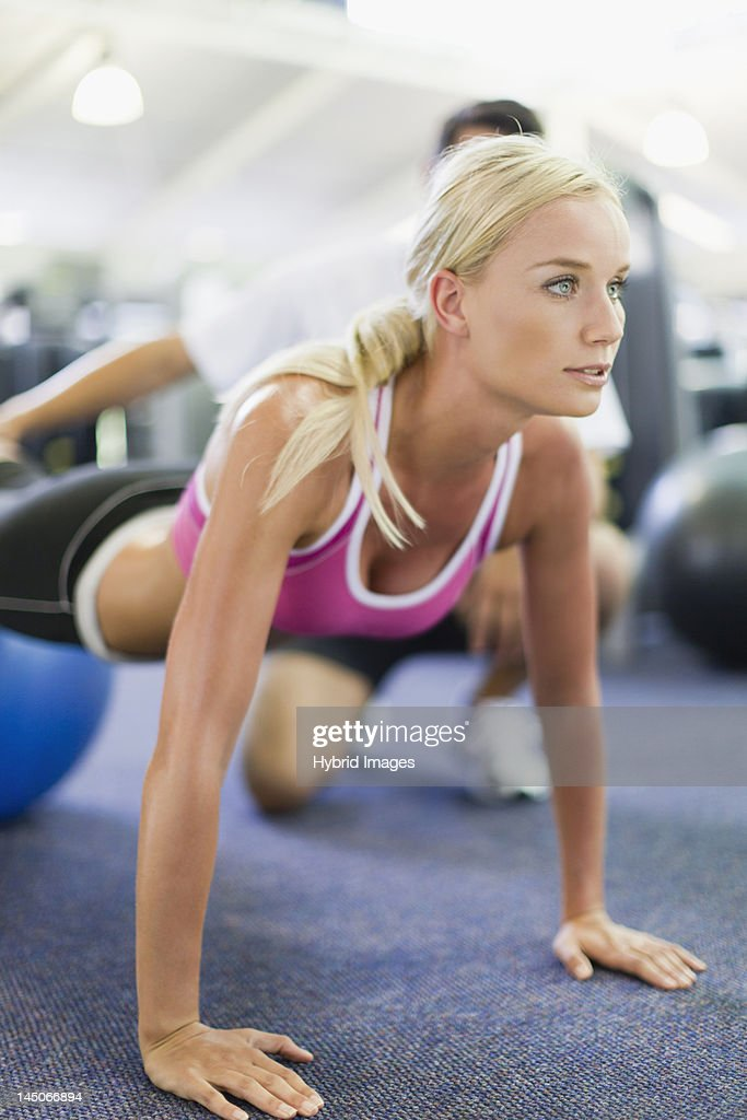 Woman working with trainer in gym : Stock Photo