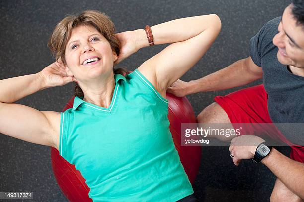 Frau Training mit trainer im Fitnessraum
