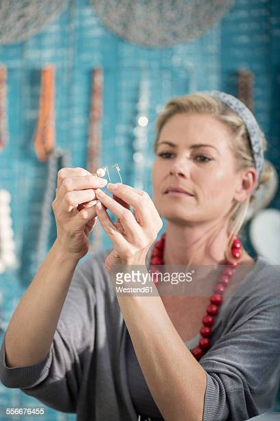 Woman working with wire to create a bead necklace