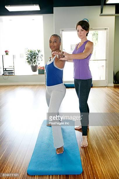 Woman working with yoga teacher in studio