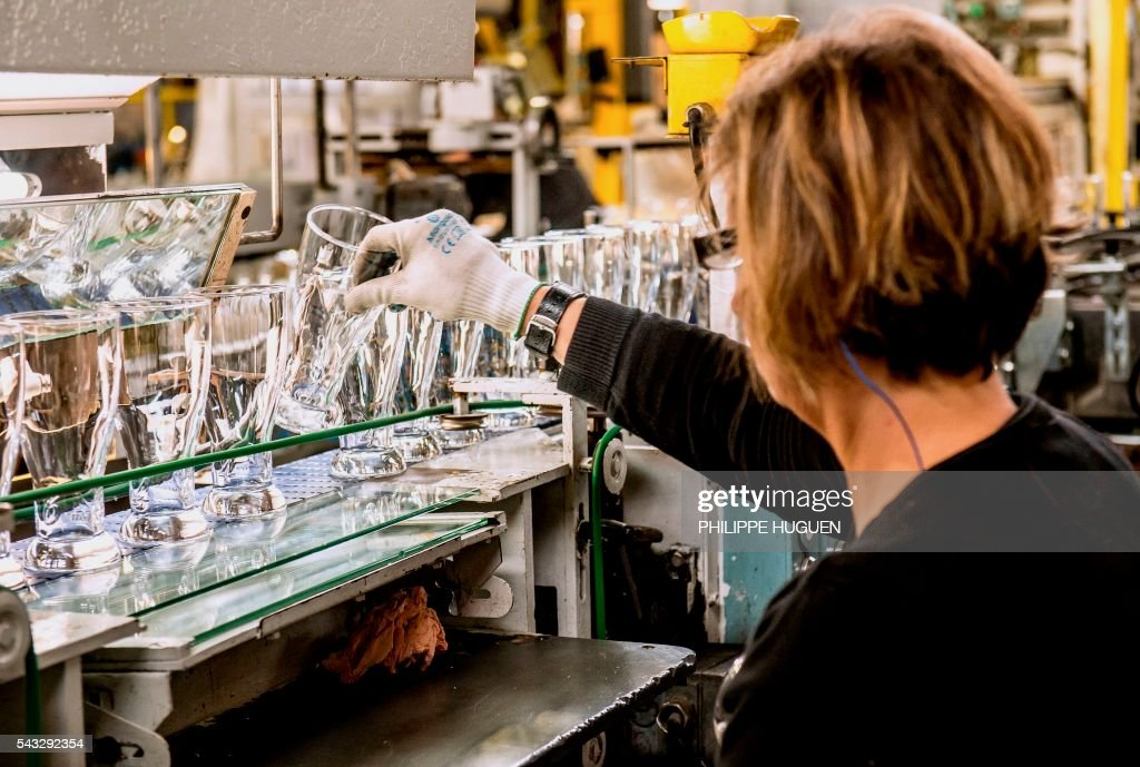 A woman works at the glass-making company Arc International in Arques, northern France, on June 27, 2016. / AFP / PHILIPPE