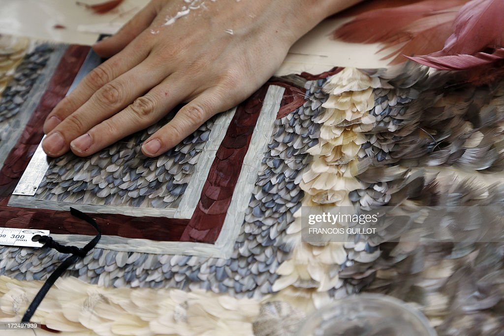A woman works on a composition of feathers on June 17, 2013 at the Maison Lemarie, in Paris. Founded in 1880 and purchased by Chanel in 1996, Lemarie is one of the last artisanal house remaining in France which is specialized in feathers and flowers for haute couture. AFP PHOTO / FRANCOIS GUILLOT