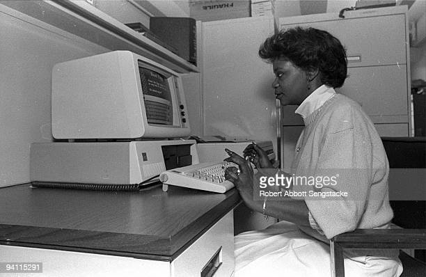 A woman works on a computer in the Amalgamated Publishers Inc office New York ca1980s The computer is an early version of a desktop terminal