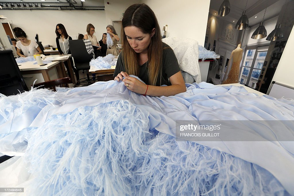 A woman works on a feather dress on June 17, 2013 at the Maison Lemarie, in Paris. Founded in 1880 and purchased by Chanel in 1996, Lemarie is one of the last artisanal house remaining in France which is specialized in feathers and flowers for haute couture.