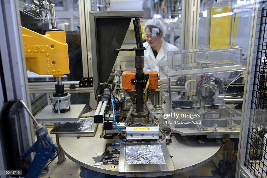 A woman works on a manufacturing robot of a photovoltaic unit in the French solar panel maker PhotoWatt in Bourgoin-Jallieu, southeastern France, on January 31,2013.