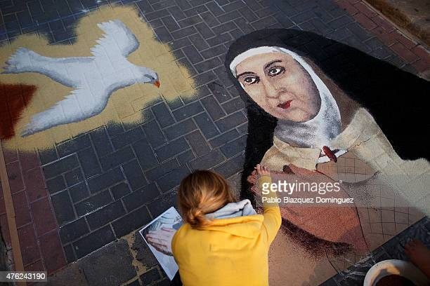 A woman works on a sawdust carpet depicting Saint Teresa of Avila in the early hours along the streets during the Corpus Christi feast on June 7 2015...