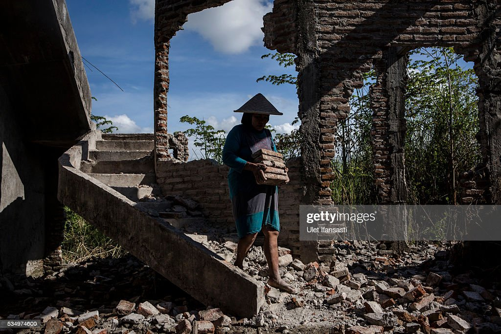 A woman works on the demolition site of a house on May 27, 2016 in Sidoarjo, East Java, Indonesia. Residents of villages that were damaged by the Sidoarjo mudflow and residents received compensation, after almost ten years, from the Indonesian oil and gas company, PT Lapindo Brantas. The mudflow eruption is suspected to have been triggered by the drilling activities of oil and gas company, though they refute the claims, instead blaming a 6.3 magnitude earthquake that struck a neighboring city two days before the mudflow eruption. The earthquake struck Yogyakarta on May 27th, 2006, a city 150 miles west of a drill site in Sidoarjo, two days before the mudflow eruption. According to reports, twenty lives were lost and nearly 40,000 people displaced, with damages topping $2.7 billion. Ten years since the eruption, the mud geysers continue to spurt daily and high levels of heavy metals have been detected in nearby rivers.