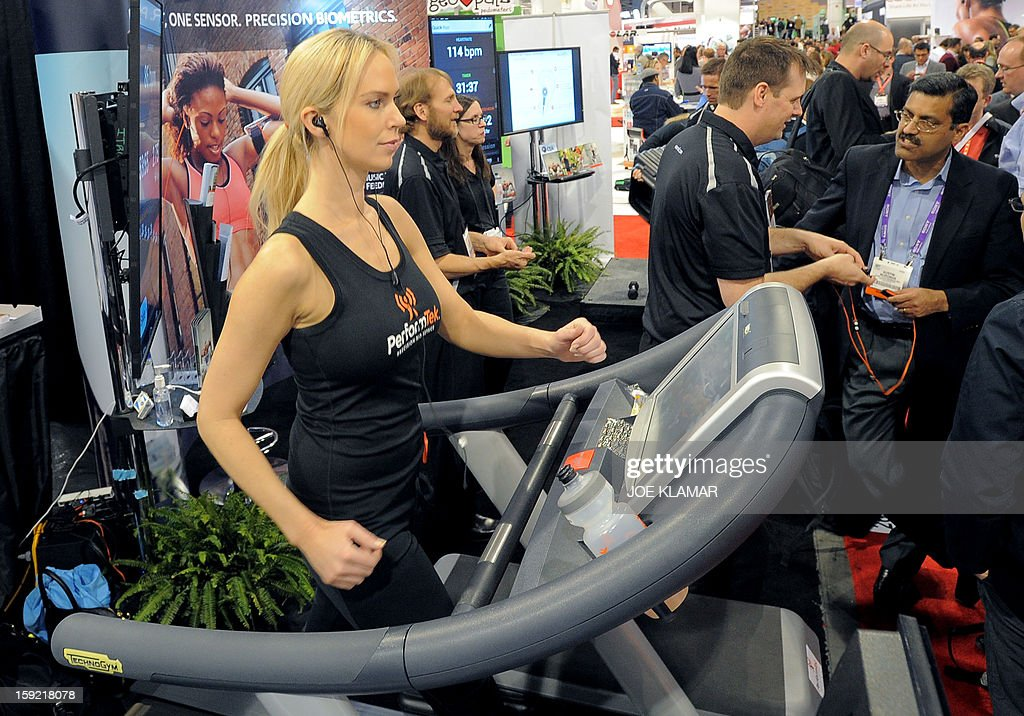 Woman works out while her pulse and callories are monitored by PerformTech earbuds made by Valencell at the Las Vegas Convention Center on January 9, 2013 in Las Vegas, Nevada. CES, the world's largest annual consumer technology trade show, runs from January 8-11 and is expected to feature 3,100 exhibitors showing off their latest products and services to about 150,000 attendees.AFP PHOTO / JOE KLAMAR