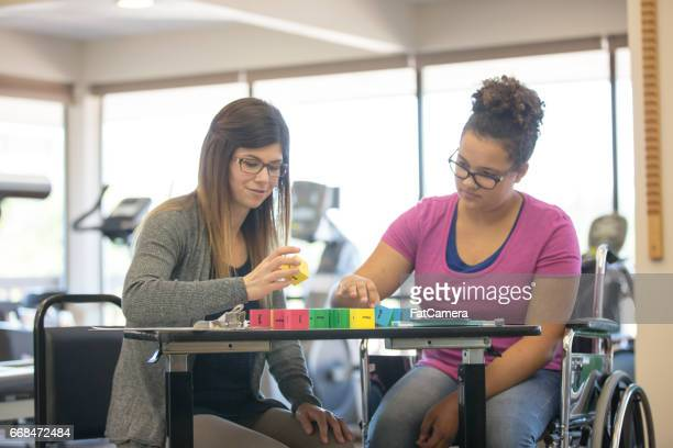 Woman works with teenage girl at rehab clinic