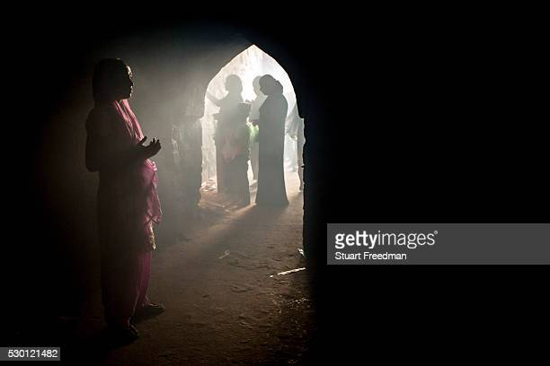 A woman worships in the ruins of the Feroz Shah Kotla Fort In New Delhi India In the niches and alcoves of its stone walls believers both Hindu and...