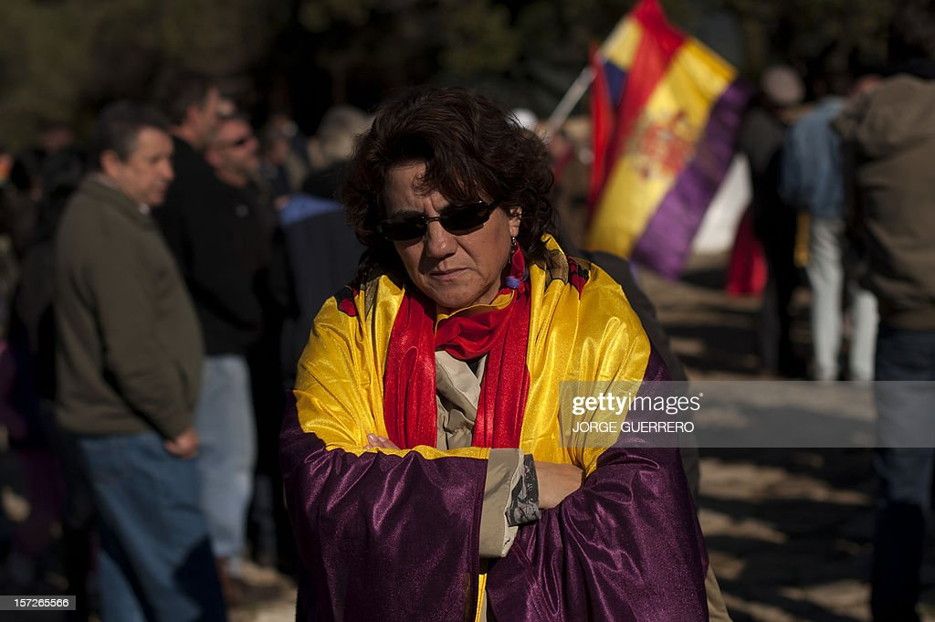 A woman wrapped in a flag of the Second Spanish Republic attends the funeral ceremony for 28 people executed during the Spanish Civil War at La Sauceda Cemetery in Cortes de la Frontera on December 1, 2012. Twenty-eight, seven women and 21 men, of the hundreds of people who were tortured and executed by the forces of Francisco Franco at the 'El Marrufo Estate' in Cadiz during the Spanish Civil war, received a proper burial today, 76 years after their bodies, all shot, were thrown into mass graves. AFP PHOTO / JORGE GUERRERO