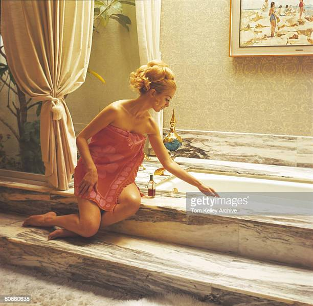 A woman wrapped in a towel sits on the edge of the tub in a luxurious bathroom and tests the water temperature with her hand mid 1970s