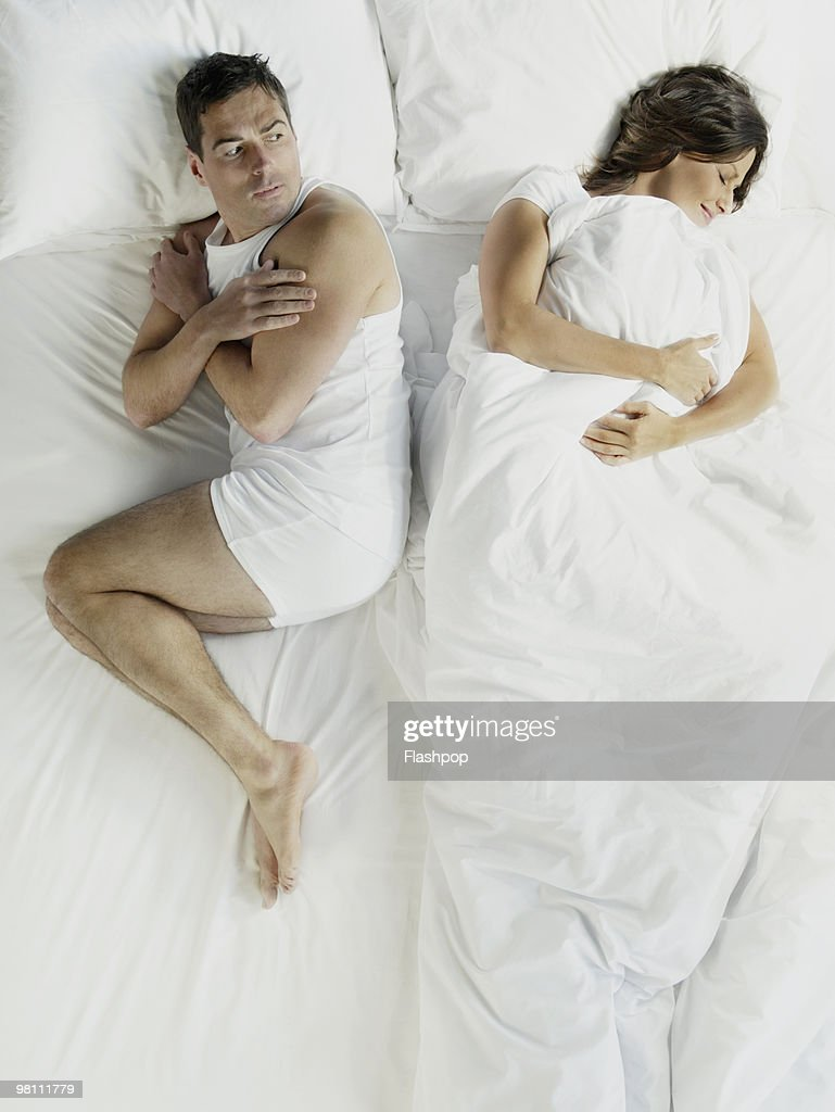 Woman wrapped in bed sheets, man shivering : Stock Photo