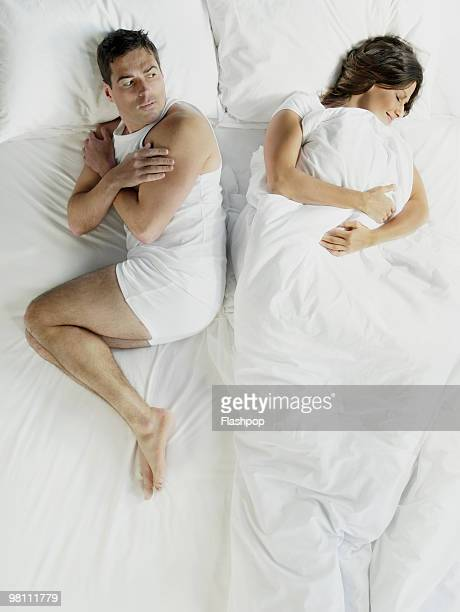 Woman wrapped in bed sheets, man shivering