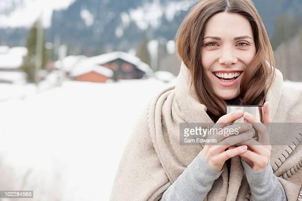 Frau trinkt Kaffee in Decke gewickelt