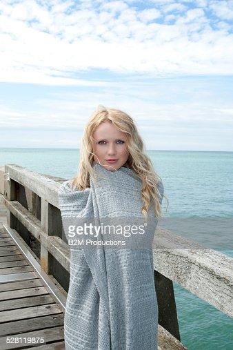 Woman wrapped in blanket on pier