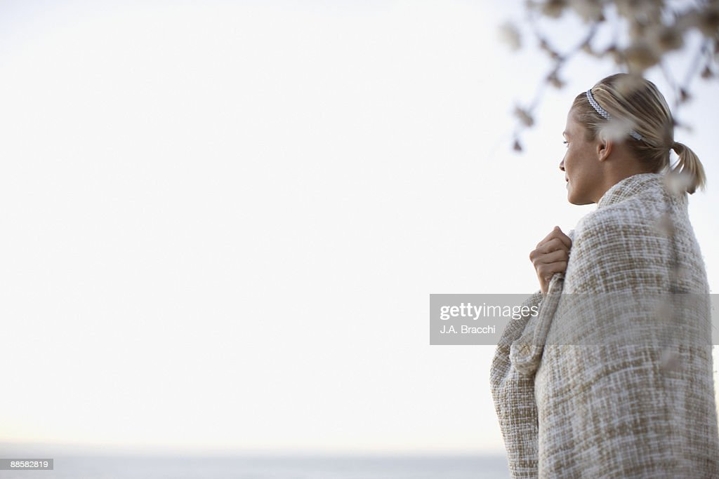 Woman wrapped in blanket outdoors : Stock Photo