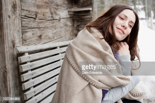 Woman wrapped in blanket sitting on bench