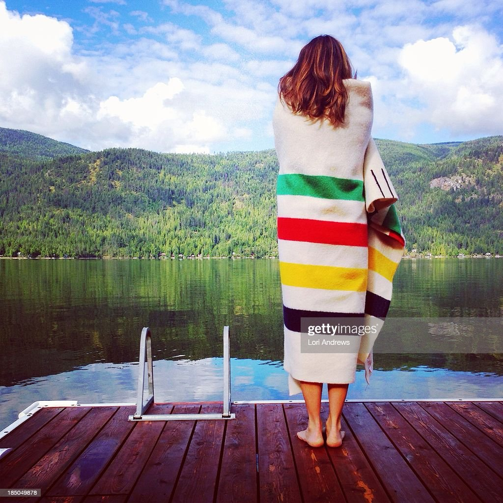 Woman wrapped in blanket standing on a dock
