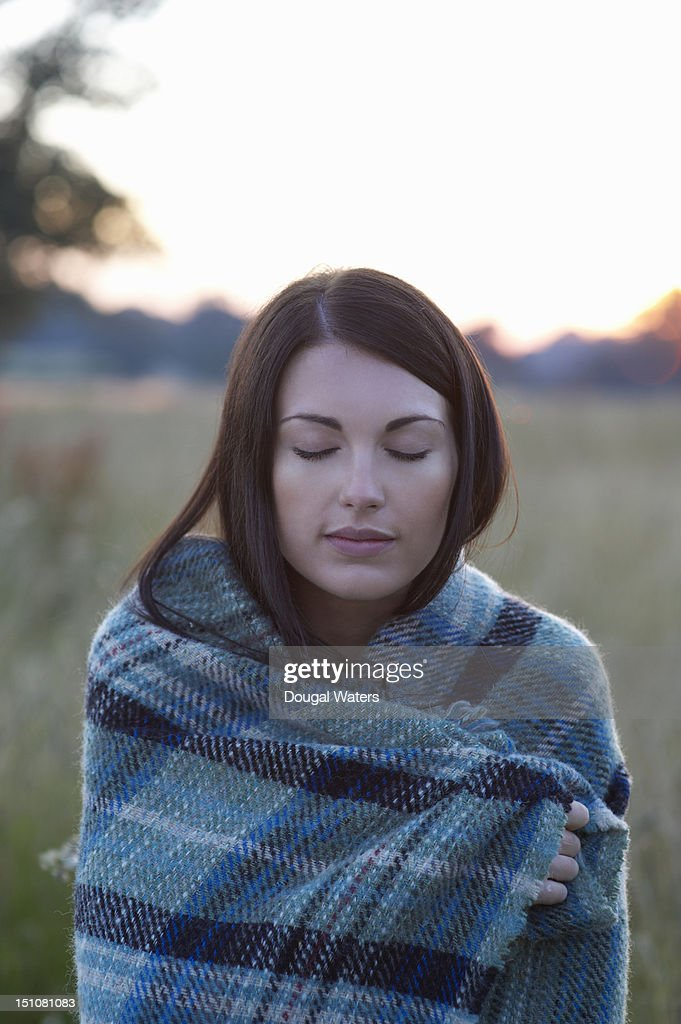 Woman wrapped in blanket with eyes closed.